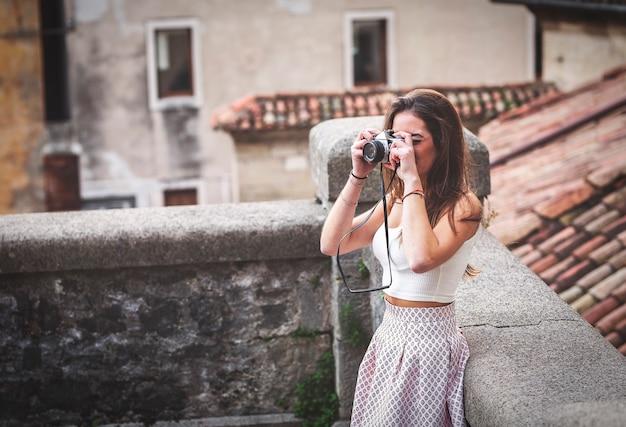 Schöner tourist mit vintage-kamera um die straßen des zentrums.