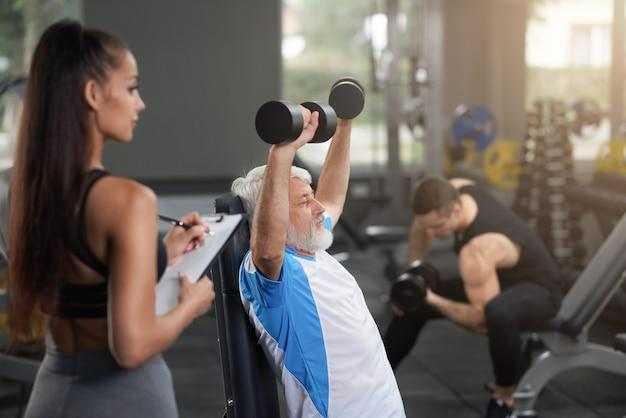 Schöner trainer, älteren mann beobachtend, übungen zu tun.
