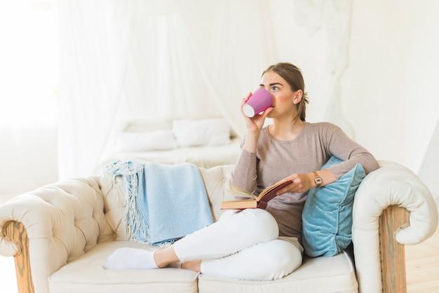 Schöner trinkender kaffee der jungen frau beim halten des buches