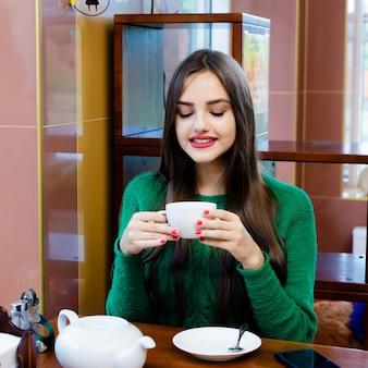 Schöner trinkender tee der jungen frau im café