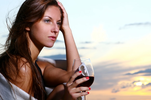Schöner trinkender wein der jungen frau auf strand
