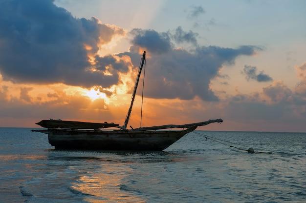 Schöner tropischer sonnenuntergang mit boot im ozean