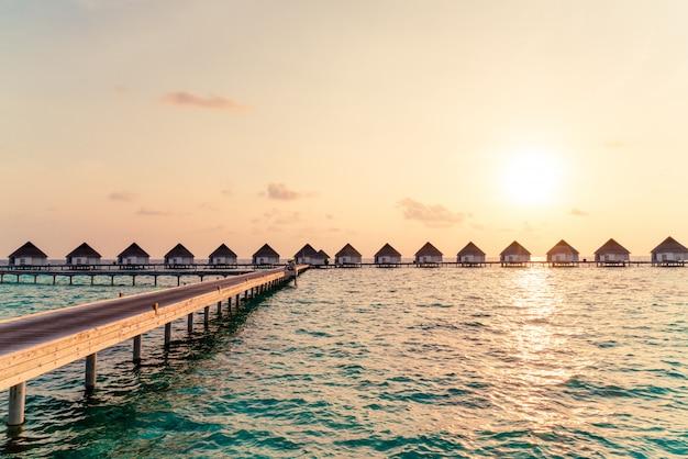 Schöner tropischer sonnenuntergang über malediven-insel mit wasserbungalow im hotelerholungsort