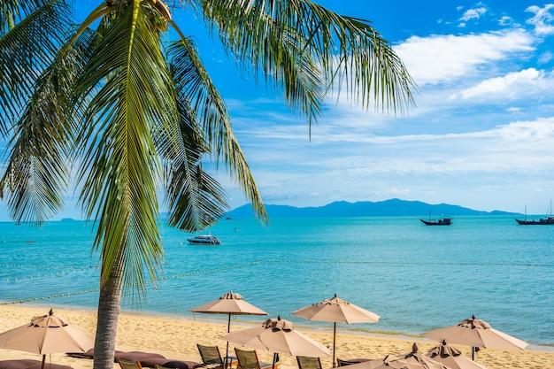 Schöner tropischer strand mit kokosnussbaum und regenschirmen