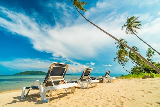 Schöner tropischer strand und meer mit kokosnusspalme und stuhl in der paradiesinsel