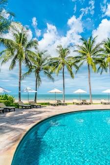 Schöner tropischer strand und meer mit sonnenschirm und stuhl um swimmingpool im hotelresort für reisen und urlaub