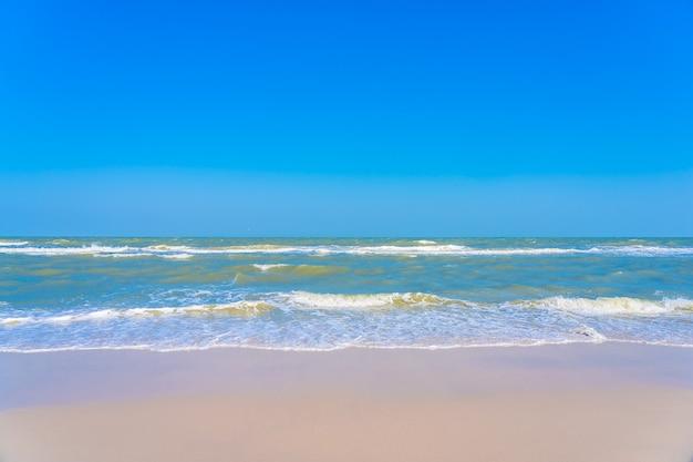 Schöner tropischer strandmeeresozean mit palme auf blauem himmel