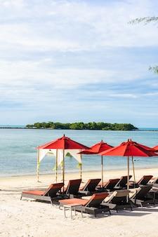 Schöner tropischer strandmeerozean im freien mit regenschirmstuhl und aufenthaltsraumplattform