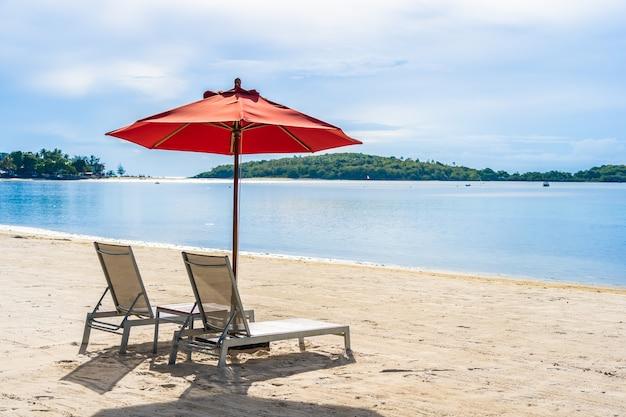 Schöner tropischer strandseeozean im freien mit regenschirmstuhl und aufenthaltsraumplattform herum dort auf blauem himmel der weißen wolke