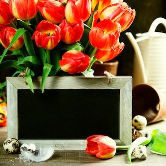 Schöner tulpenstrauß, ostereier und gartengeräte auf holztisch