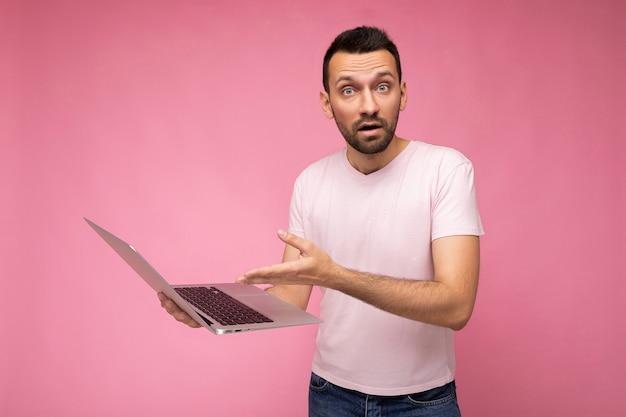 Schöner überraschter und überraschter mann, der laptop-computer hält