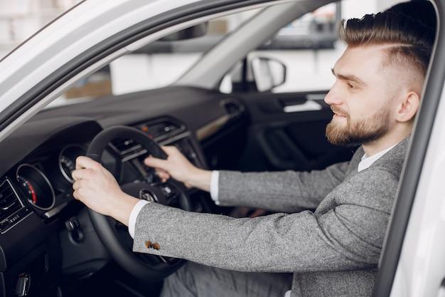 Schöner und eleganter mann in einem autosalon