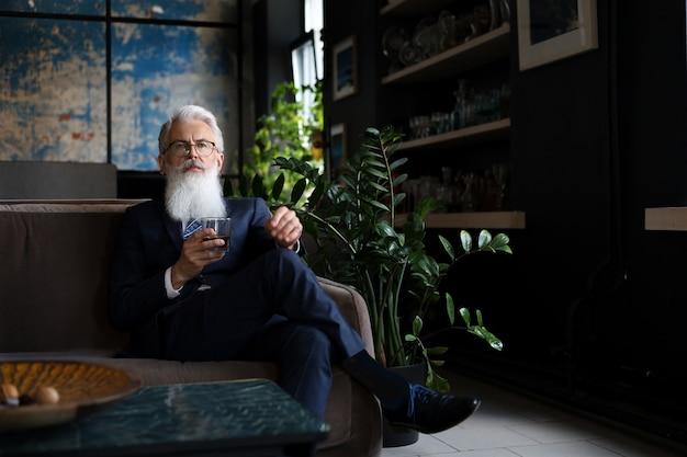 Schöner und erfolgreicher geschäftsmann mit stilvollem bart im anzug, der ein glas whisky hält, während er auf dem sofa im büro sitzt.