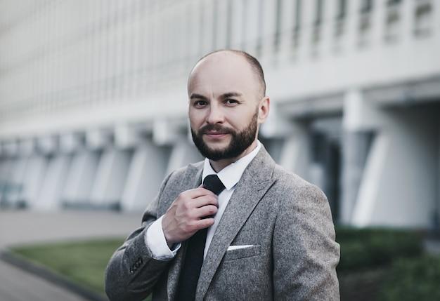 Schöner und erfolgreicher mann in einem teuren anzug. er trägt ein weißes hemd mit krawatte.