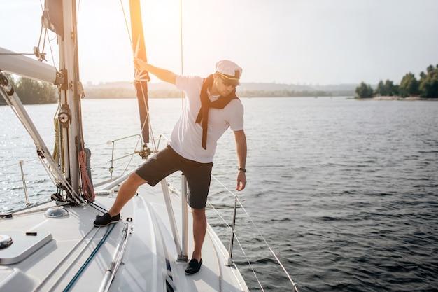 Schöner und ernster seemann, der auf seiner yacht steht. er hält sich an der röhre fest und schaut auf den rand des bootes. junger mann posiert.