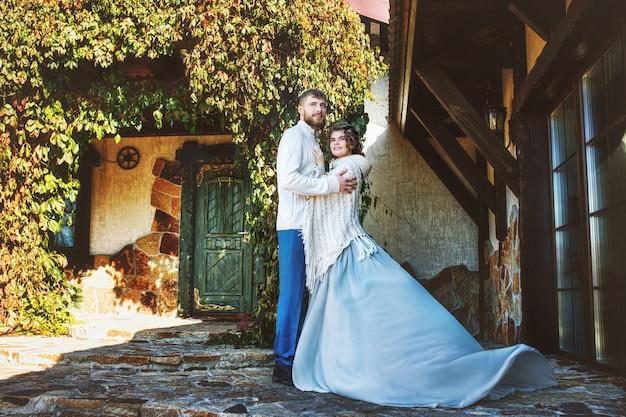 Schöner und glücklicher junger paarmann und -frau in einem schönen garten im hof eines landhauses