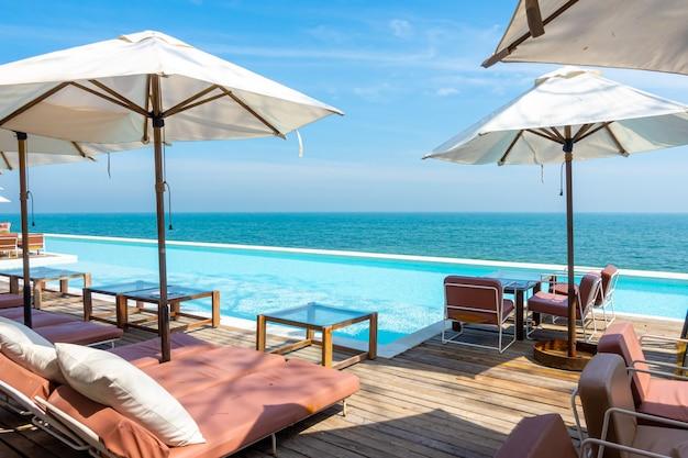 Schöner und leerer stuhl und sonnenschirm mit swimmingpool und meeresstrand