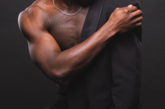 Schöner und muskulöser schwarzer mann auf dunkelheit
