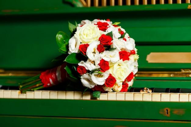 Schöner und niedlicher brautstrauß, der auf dem klavier liegt