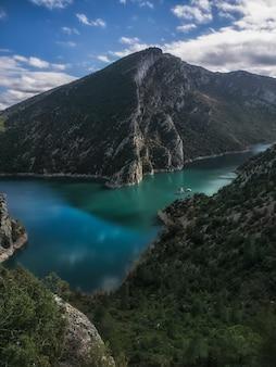 Schöner und ruhiger smaragdgrüner fluss, vor einem berg und einem wald in der nähe in katalonien, spanien