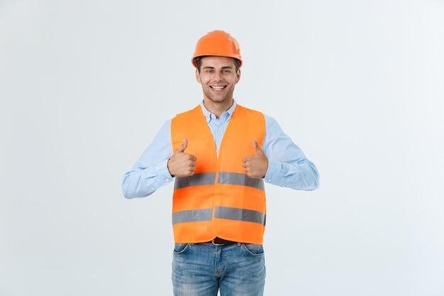 Schöner und selbstbewusster berufsarbeiter, der daumen hoch zeigt oder wie geste lächelt glücklich isoliert auf weißem hintergrund.