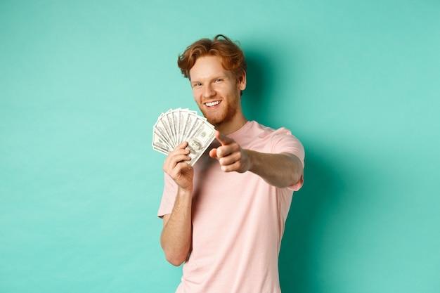 Schöner und selbstbewusster rothaariger, der mit dem finger auf sie zeigt, gelddollar zeigt und ein lächelndes konzept zeigt ...