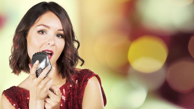Schöner und stilvoller frauensänger mit einem mikrofon