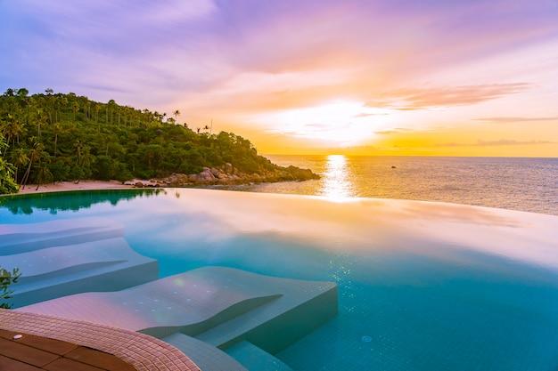 Schöner unendlichkeitsswimmingpool im freien im hotelerholungsort mit seeozeanblick und blauem himmel der weißen wolke