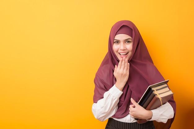 Schöner universitätsstudent mit hijab auf gelber wand