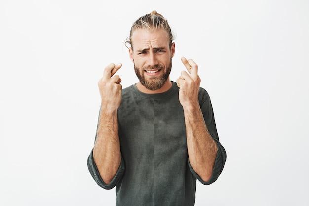 Schöner unrasierter mann, der finger mit besorgtem ausdruck gekreuzt hält
