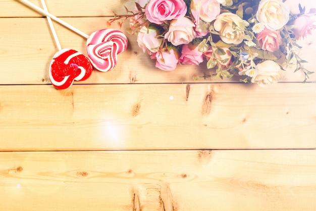 Schöner valentinstaghintergrund mit schatzen auf hölzernem hintergrund