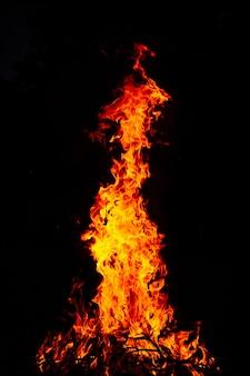 Schöner vertikaler schuss eines großen brennenden feuers in der nacht