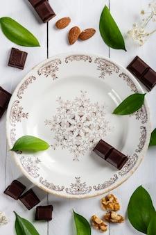 Schöner vintage-teller auf einem weißen holztisch, bedeckt mit schokoladenstücken, walnüssen, mandeln und blättern aus der natur