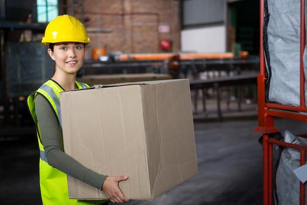 Schöner weiblicher arbeiter, der kasten im lager trägt