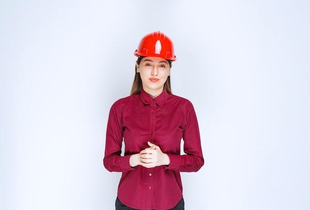 Schöner weiblicher architekt im roten harten sturzhelm, der kamera über weißer wand betrachtet.