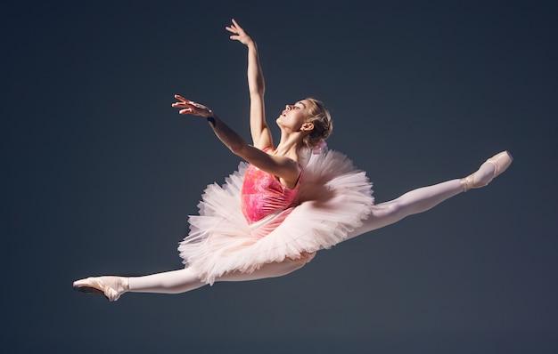 Schöner weiblicher balletttänzer auf einem grauen hintergrund