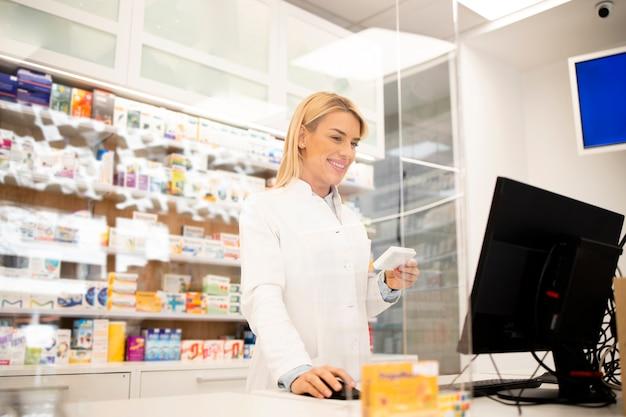 Schöner weiblicher blonder apotheker, der im apothekenladen steht und medikamente verkauft.
