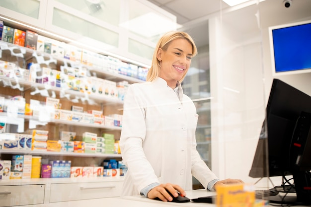 Schöner weiblicher blonder apotheker, der in drogerie steht und medikamente verkauft.