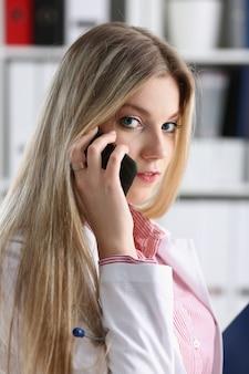 Schöner weiblicher blonder doktor, der am telefon in der bürofrau bespricht die krankheit und gibt fernschulungsbildung der on-line-beratung spricht