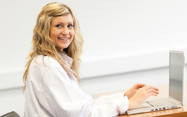 Schöner weiblicher chirurg, der an einem laptop arbeitet