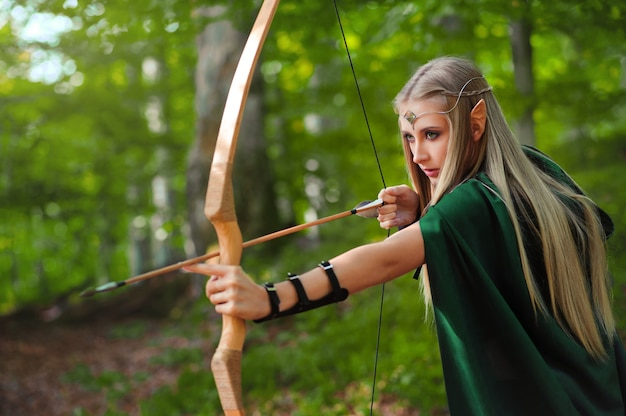Schöner weiblicher elfenbogenschütze im wald, der mit einem bogen jagt