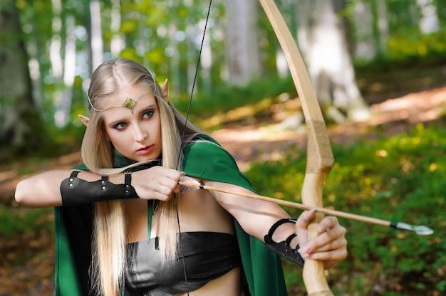 Schöner weiblicher elfenbogenschütze im wald, der mit einem bogen jagt Premium Fotos