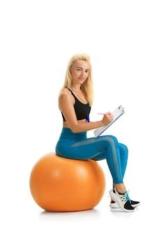 Schöner weiblicher fitness-trainer, der isoliert auf weißem studio übt