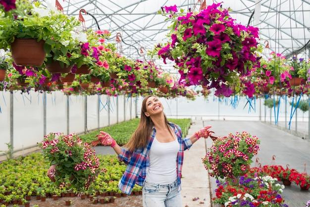 Schöner weiblicher florist, der topfblumenpflanzen im gewächshaus hält, das glücklich und positiv fühlt