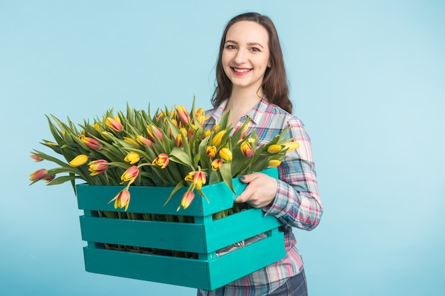 Schöner weiblicher gärtner, der kasten mit tulpen auf blauem hintergrund hält