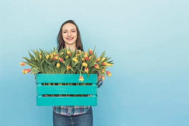 Schöner weiblicher gärtner, der kasten mit tulpen auf blauem hintergrund mit kopienraum hält