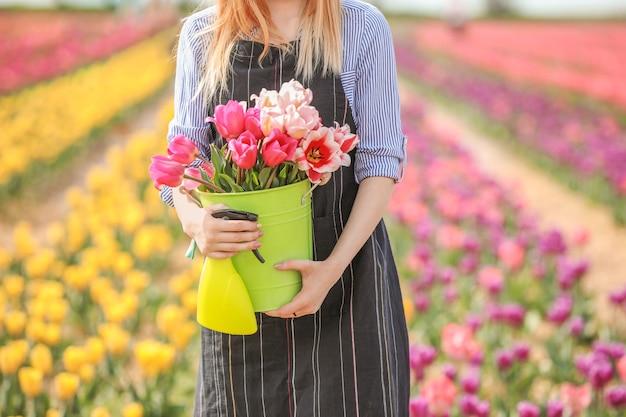 Schöner weiblicher gärtner im tulpenfeld am frühlingstag
