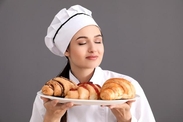 Schöner weiblicher koch, der teller mit croissants auf grauer oberfläche hält