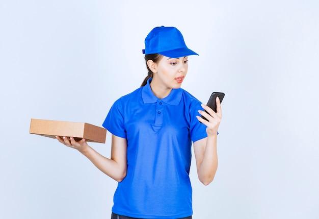 Schöner weiblicher kurier, der kartonpaket hält und eine nachricht sendet.