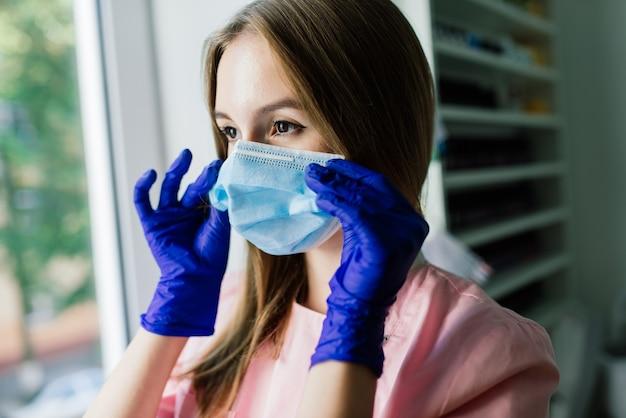 Schöner weiblicher medizinischer arbeiter oder maniküremeister in der medizinischen maske